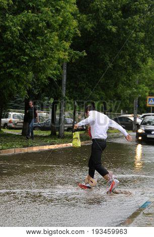 KOROLEV MOSCOW REGION RUSSIA - JUNE 30 2017: Unidentified man walks across flooded street wearing plastic bags on his feet