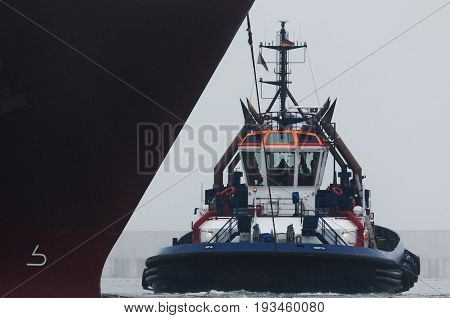 TUG AND GAS TAKER - The tug  maneuver at the bow of a large ship