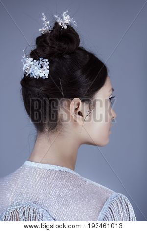 Profile of futuristic young woman. Beautiful young multi-racial asian caucasian model girl in silver urban clothes with conceptual hairstyle and make-up against blue copy-space background. Side view.