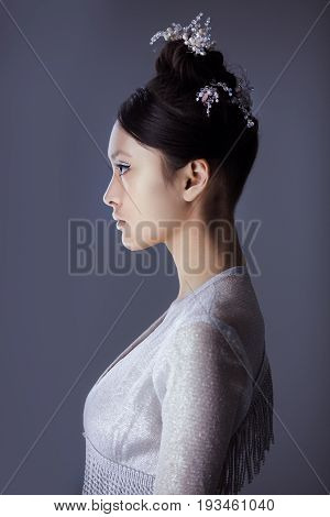 Profile of futuristic young woman. Beautiful young multi-racial asian caucasian model cyber girl in silver urban clothes with conceptual hairstyle and make-up against blue copy-space background. Side view.