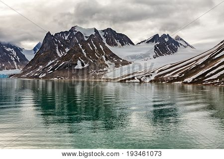 Cloudy sky over the mountains along the Magdalenafjord in Svalbard islands Norway