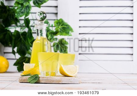 Italian traditional liqueur with lemons on a wooden background. Selective focus.