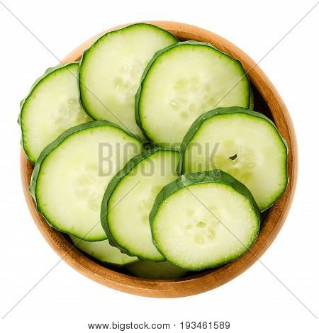 Cucumber slices in wooden bowl. Cucumis sativus. Sliced seedless vegetable, fresh and unripe with green skin. Isolated macro food photo close up from above on white background.