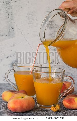Freshly prepared natural peach juice with pulp in a glass jug and in a mug, next to ripe peaches on a dark wooden table. The concept of healthy eating.  Selective focus.