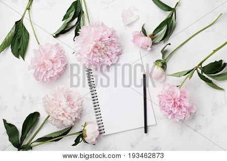 Empty notebook for wedding planning pencil and pink peony flowers on white stone table top view in flat lay style. Woman working desk.