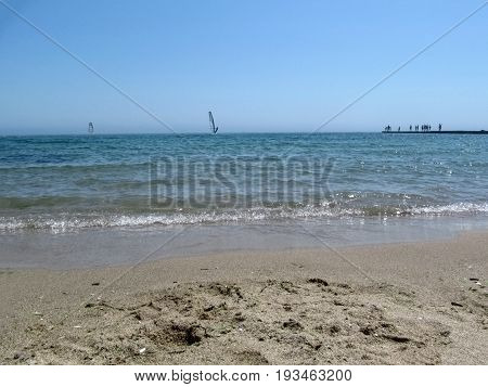 Seascape with windsurfer on the horizon. Clean sand the blue sea the sky and small silhouettes of people in the distance who look at the windsurfing