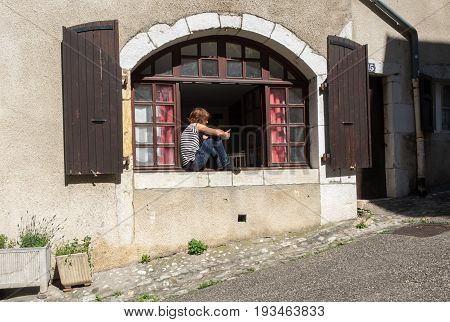 ANNECY FRANCE - JUNE 17 2017: Undefined young man sit in medieval building window in Annecy at Haute-Savoie department. France