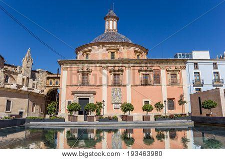 Colorful Basilica De La Virgen With Reflection In The Water In Valencia