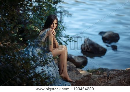 Woman at water. Model Girl Portrait in Moonlight at Night. Sexy Glamour Mystical Beautiful Woman in blue dress sitting on a beach against water background. Beautiful fashion creative shot of seductive multi-racial Asian Caucasian sexy female. Girl looking