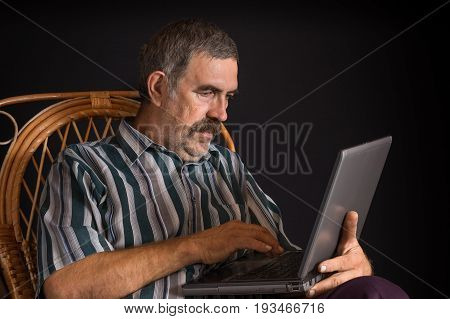 Portrait of mature Ukrainian peasant sitting in wicker chair and typing on a laptop PC