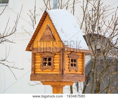 Wooden house - a bird feeder in a winter park