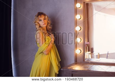 Pregnant woman. Romantic portait photo of beautiful blonde girl posing in sexy evening dress looking away at home. Indoor shot against gray wall and mirror.