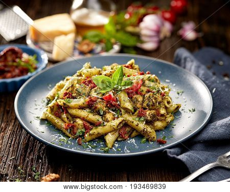 Penne pasta with spinach, sun dried tomatoes and chicken, sprinkled with parmesan cheese and fresh parsley