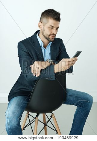 Businessman looking at smart phone isolated stock photo.