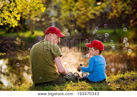 Father and son are sitting on the shore of the lake let the soap bubbles