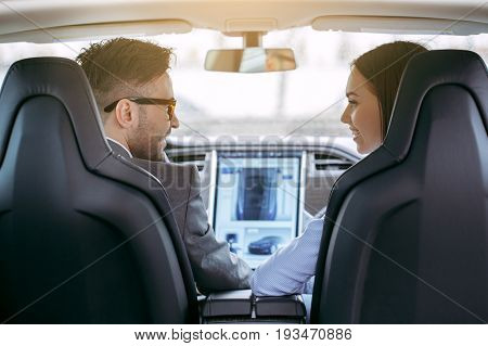 Man and woman transportation by modern eco car control panel