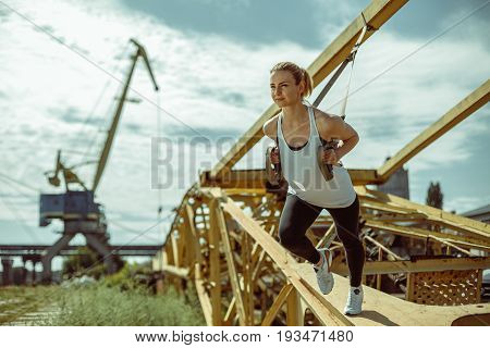 Cheerful woman exercising with suspension trainer outdoor. Trx training against the background of metal parts.