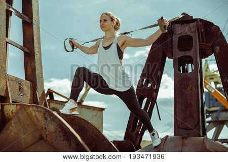 Beautiful athletic woman doing exercise with trx system. Young woman exercising with suspension trainer outdoors.