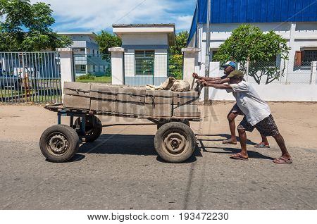 Toamasina Madagascar - December 22 2017: Unidentified Madagascar men push huge carriage with bricks in Toamasina (Tamatave) Madagascar East Africa. People in Madagascar suffer of poverty due to the slow development of the country.