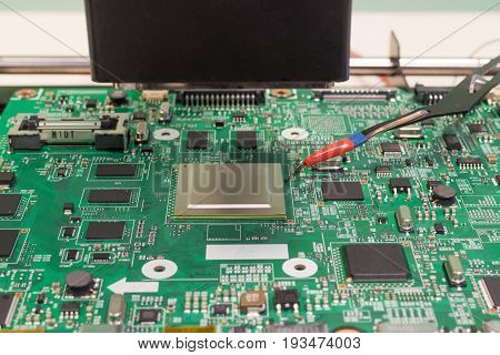 TV repair. Soldering an electronic chip on an infrared rework soldering station
