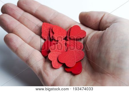 In hand many red hearts on a white background.