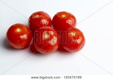 Shriveled cherry tomatoes on a white background.