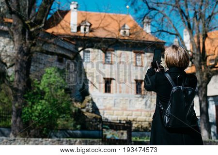 Young caucasian woman traveling through Czech Republic and taking digital photo with smartphone in Cesky Krumlov. Overview of town from Castle