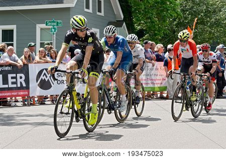 STILLWATER, MINNESOTA - JUNE 18, 2017: Group of pro cyclists in peloton chase leaders at the 2017 North Star Grand Prix Men's Stillwater Criterium. It is the final stage of a six-stage annual race.
