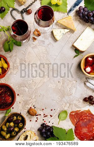 Wine and snack set. Variety of cheese, mediterranean olives, prosciutto,baguette slices, black and green grapes, sun-dried tomatoes, peppers and glasses of red wine