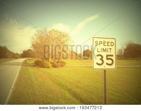 A speed sign on a scenic country road with a home in a vintage background.