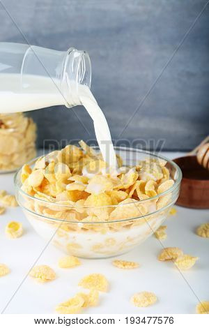 Pouring Milk In Bowl Of Cornflakes On Wooden Table