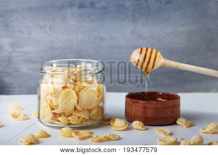Cornflakes In Glass Jar With Bowl Of Honey On Grey Background