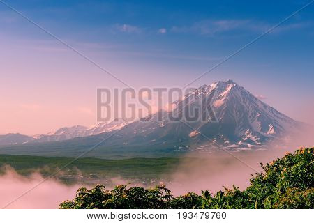 Hazed Koryak volcano above fog. Kamchatka peninsula.