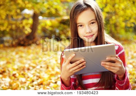 portrait of a teenage girl with tablet computer in autumn outdoor