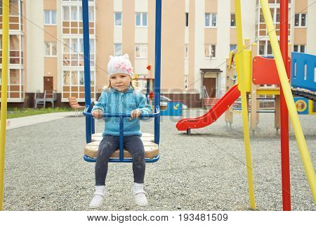 sad little girl on playground. child swinging on a swing