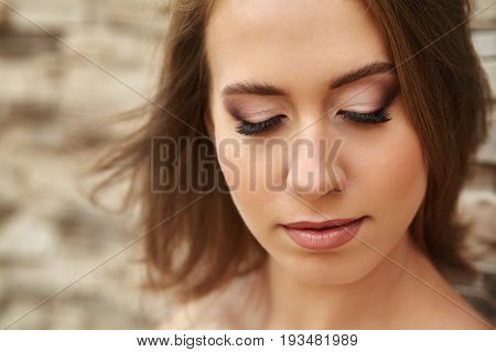 Portrait of a young woman with long artificial extended lashes