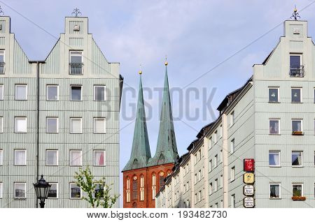 Berlin, Germany - April 15, 2017: Modern white buildings and the spire of St. Nicholas Church in perspective.