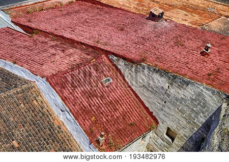 Looking down on colorful abstract pattern of terracotta roof tiles of buildings in Porto Mahon Menorca Spain