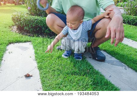 Cute little Asian 1 year old toddler baby boy child playing in the park with snail at day time. He having fun on the garden. Concept of kid is ready to go to school Dad and Son spending time outdoor