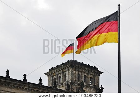 Two German flags on the background of the Reichstag in Berlin Germany.