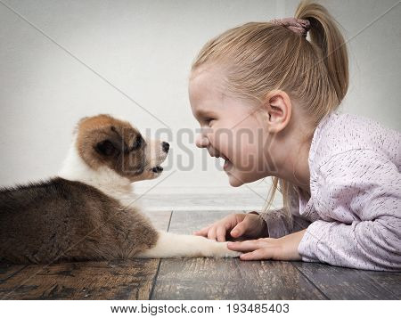 happy child and a small puppy lying on the floor facing each other. The girl gently strokes the dog's paw and laughs