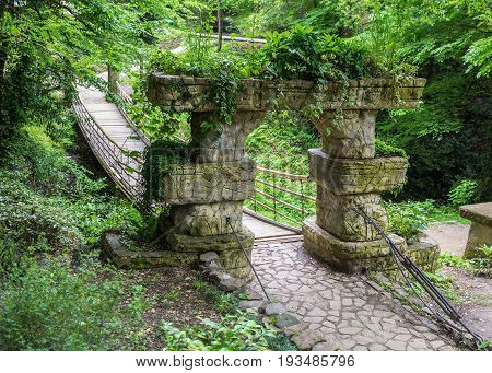 Wooden hanging bridge in the garden. Entrance to the bridge is decorated with stone arch support