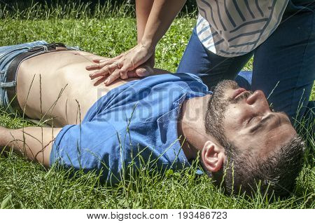 girl helping an unconscious guy with cpr and cardiac massage