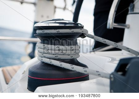 Sailing boat winch with rope closeup in the open sea