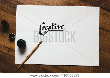 Creative artist workplace. Ink handwritten word and pen top view. Painter workshop, art business inspiration, creativity, handmade drawing concept