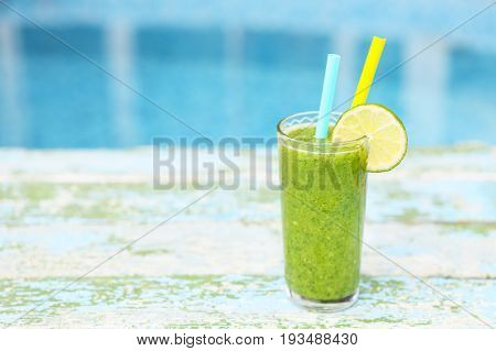Freshly blended green fruit smoothie in glass with straw. Turquoise blue background copy space