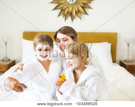 Happy mother and girls in bathrobes in room after shower making selfie