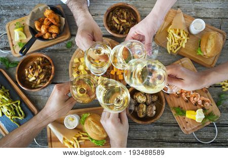 Hands with white wine toasting over served table with food. Friendship and happiness concept