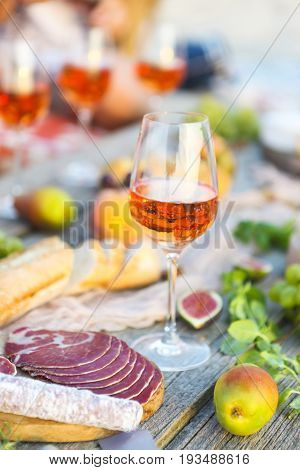 Glass of rose wine and Italian food on wooden table