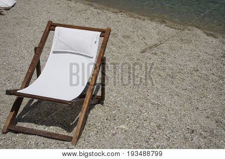 Wooden beach chair for tanning by the sea on a pebble beach. Chaise longue deck beach chair with white texture seating on a summer sunny day.